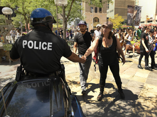 A protester shakes hand with a Denver Police officer during a peaceful demonstration July 11, 2016 downtown Denver.