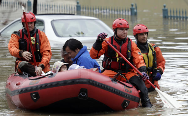 Rescuers sometimes chest-deep in water steered boats carrying dozens of people, including babies and pets, from a San Jose neighborhood inundated by water from an overflowing creek.