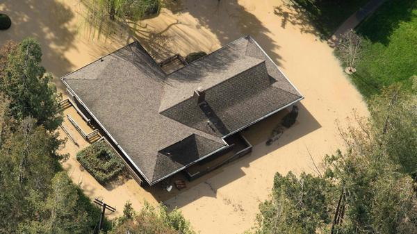 Floodwaters surround a home in San Jose, Calif., on Wednesday. Thousands of people were ordered to evacuate their homes as floodwaters inundated neighborhoods and forced the shutdown of a major highway.