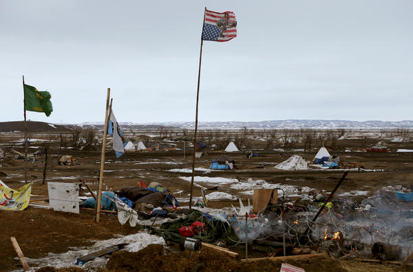 An upside-down American flag waves over a roadblock set up by protestors at the main entry to the Oceti Sakowin camp.