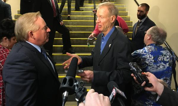 After a speech Wednesday at Springfield's Prairie Capital Convention Center, Gov. Bruce Rauner, right, stopped to talk to a conference attendee, but repeatedly refused to answer questions from reporters.
