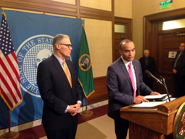 Washington Gov. Jay Inslee listens as his general counsel Nick Brown addresses questions from reporters after the governor issued an executive order Thursday.