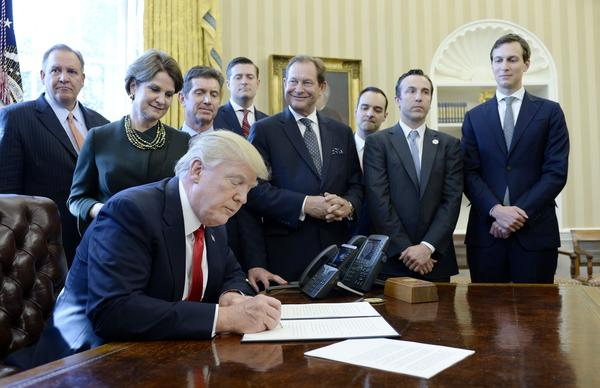 President Trump, flanked by business leaders, signs an executive order aimed at rolling back regulations across government agencies.