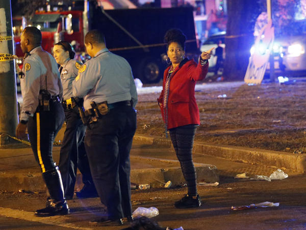 Police talk to a woman at the scene where a vehicle slammed into a crowd and other vehicles, causing multiple injuries during the Krewe of Endymion parade in New Orleans on Saturday.