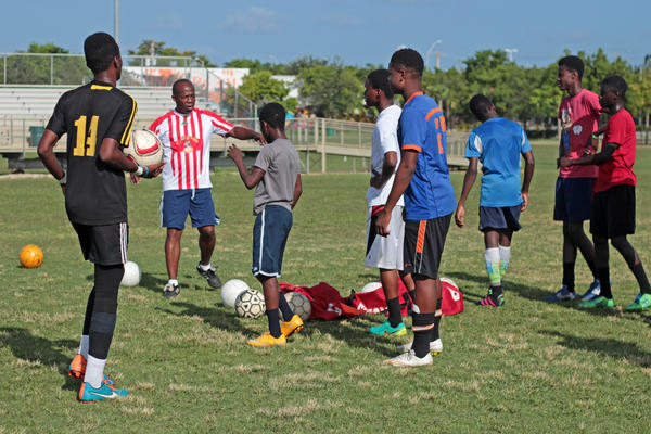 Ernst Baptiste, coach of the Little Haiti Football Club boys team, directs his players onto the field to start drills on July 27, 2016.