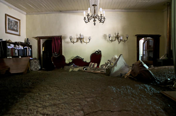 Sludge fills the living room of a home in Santiago on Sunday after rains triggered mudslides.