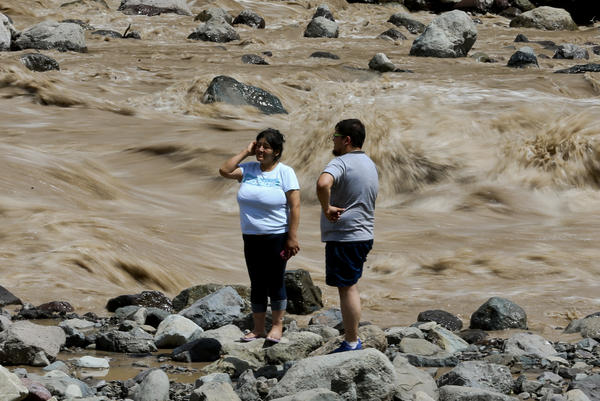 A couple looks at the overflowing Maipo River on Sunday in Santiago, where at least three people are dead and 19 others missing after heavy storms.