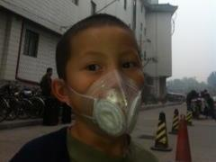 On a recent day, NPR correspondent Louisa Lim's 6-year-old son, Daniel, wears a protective mask outside.