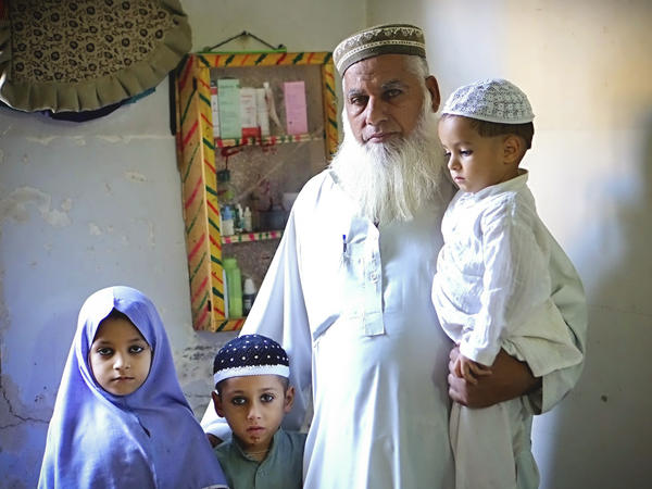 Gul Mohammed Khan has lost three sons in sectarian violence during the last two years, in Karachi, Pakistan. He stands here with some of his grandchildren who have lost their fathers. When he looks at his grandchildren, he says, he sees his sons.