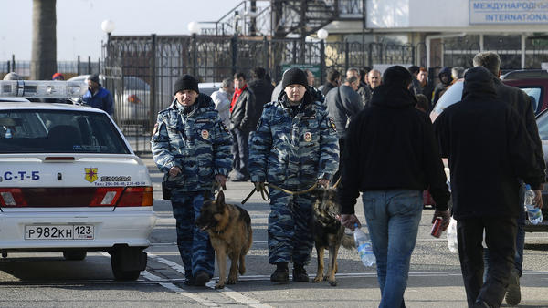Police officers with dogs walk along a street in Sochi, Russia, on Jan. 6. The presence of security personnel has ramped up recently ahead of the Winter Olympics.
