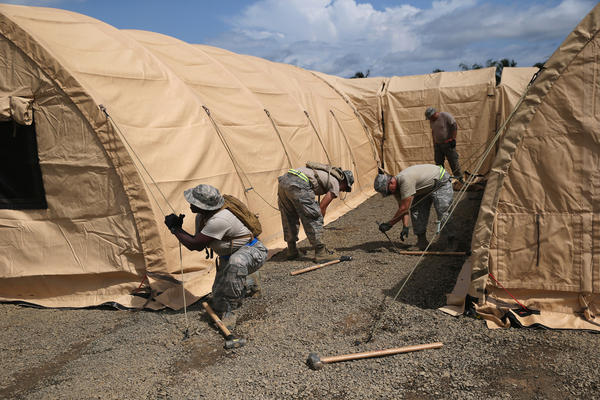 Air Force personnel put up tents to house a 25-bed, U.S.-built hospital for Liberian health workers sick with Ebola in Monrovia, Liberia's capital. The hospital is scheduled to open this weekend.