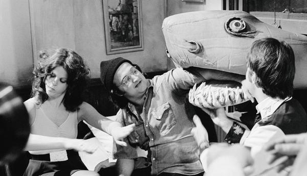 Gilda Radner pays no mind as the Land Shark gobbles John Belushi's arm backstage in 1976.