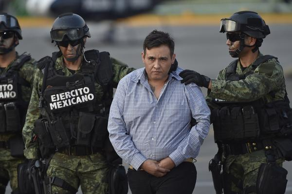The alleged leader of the Zetas drug cartel, Omar Trevino Morales, is taken under custody to be presented to the press at the Attorney General Office's hangar at the airport in Mexico City, on March 4. Mexican authorities captured Trevino Wednesday, dealing a blow to the feared gang and giving the embattled government a second major arrest in a week.