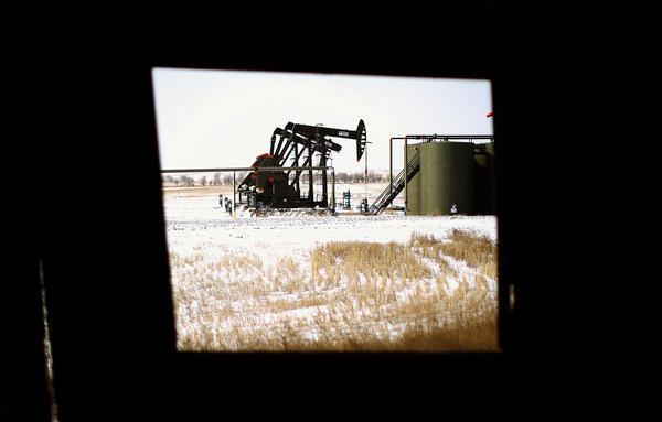 A production site in the Bakken oil patch as seen from inside an abandoned farmhouse just outside Watford City, N.D.