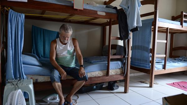 Unemployed worker Gesse Dias Lopes, 63, sits on a bed March 19 at the Workers Inn in Itaborai, Brazil, where he has been offered a place to stay for free. The crisis at the Brazilian state energy giant Petrobras has directly hit the region's economy, with sales falling by 80 percent and unemployment surging dramatically.