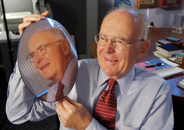 Intel Corp. co-founder Gordon Moore holds up a silicon wafer at Intel headquarters in Santa Clara, Calif., in 2005. Moore's prediction 50 years ago, called Moore's Law, has been the basis for the digital revolution.