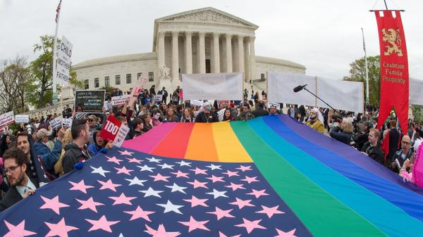 Protesters hold a pro-gay-rights flag outside the US Supreme Court on Saturday, countering the demonstrators who attended the March For Marriage in Washington, D.C. The Supreme Court meets on Tuesday to hear arguments over whether same-sex couples have a constitutional right to wed in the United States, with a final decision expected in June.