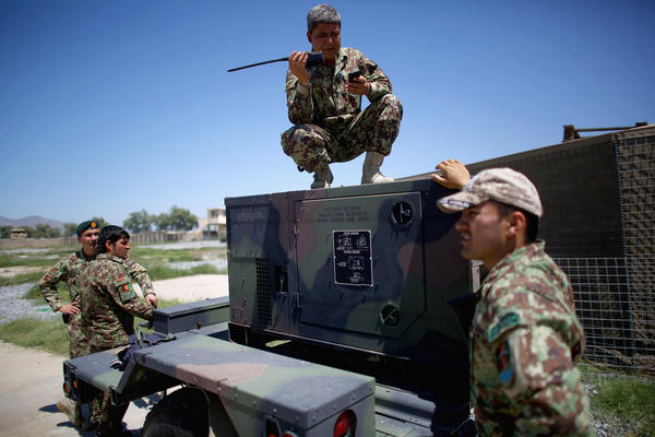 Afghan army battalion commander Lt. Col. Ghani Khel talks with his soldiers after a successful strike on a Taliban truck and rocket launcher.