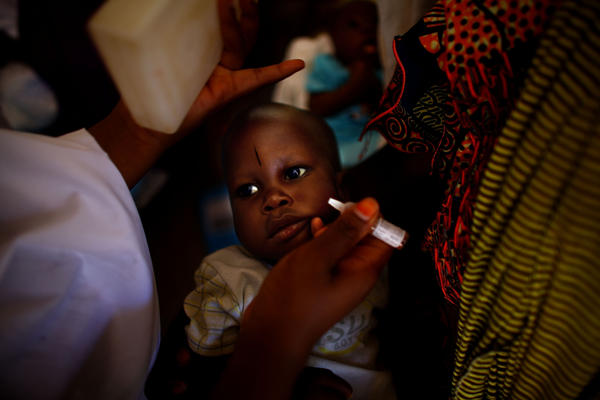 At the health clinic in Minjibir, Nigeria, a child is immunized for polio.