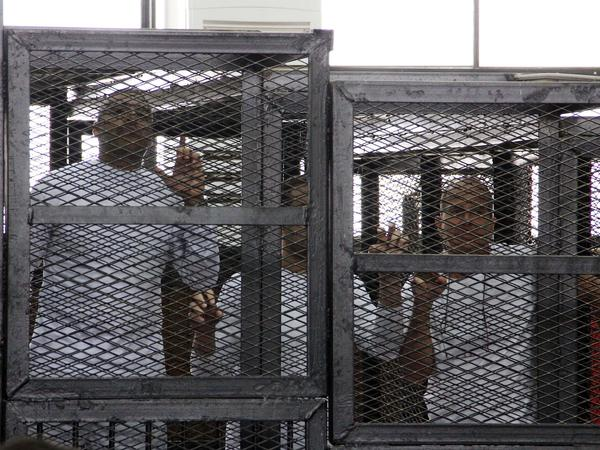 Al-Jazeera English journalists Mohammed Fahmy, left, Baher Mohamed, center, and Peter Greste, right, appeared in a cage during their trial on terrorism-related charges in Cairo in March 2014. The journalists denied all charges. Greste, an Australian, was released earlier this year, but Fahmy, a Canadian-Egyptian, and Mohamed are still on trial.