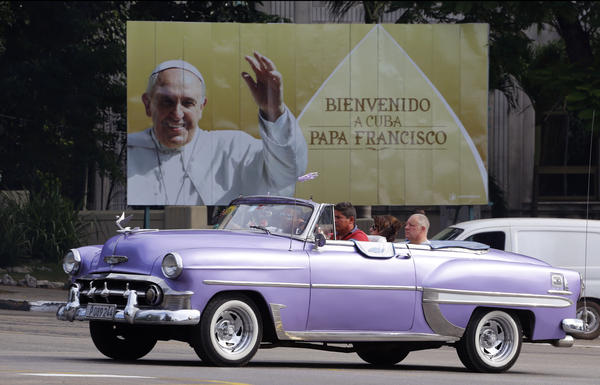 Tourists in an American classic car are driven past a billboard welcoming Pope Francis in Havana on Tuesday. The crush for the pope's visit will strain Cuba's limited tourist infrastructure.