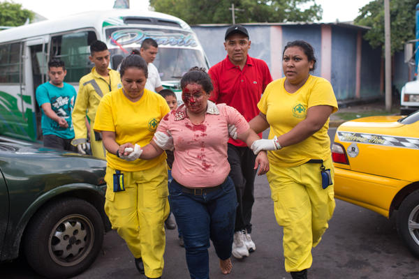 A wounded woman arrives at the offices of Comandos de Salvamento. Her companions claim she was pushed from a bus by gang members.