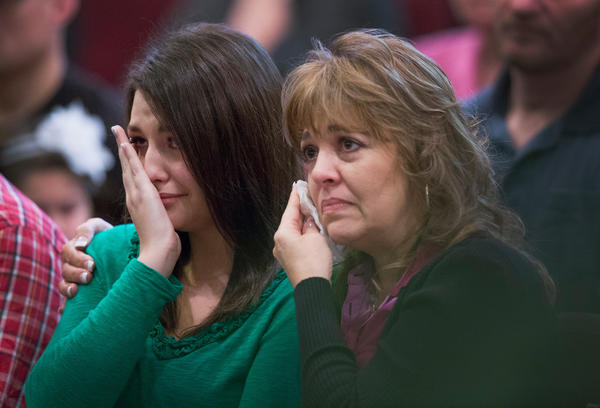 Lacey Scroggins and her mother, Lisa, listen as Lacey's father, Randy, pastor at New Beginnings Church of God, recounts in his Sunday sermon his daughter's experience during the mass shooting at Umpqua Community College in Roseburg, Ore. Lacey says she believes she survived the shooting by playing dead next to the bleeding body of fellow student Treven Anspach, who died in the shooting.