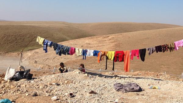 Children play as clothes hang on the line at an isolated camp for Yazidis near Dohuk, in northern Iraq. Many of the Yazidis are from the area around Sinjar, a town where Islamic State fighters have been pushed out.