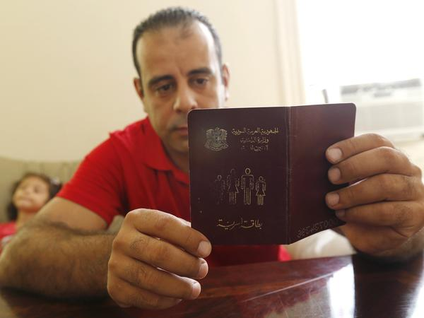 Syrian refugee Hussam Alroustom, who fled with his wife and two young children, looks over a booklet with identification information in his family's apartment in Jersey City, N.J., in September. The U.S. has resettled around 1,800 refugees from Syria in the past two years.