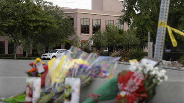Flowers are placed on Sunday near the building where last week's shooting rampage took place at the Inland Regional Center in San Bernardino, Calif.