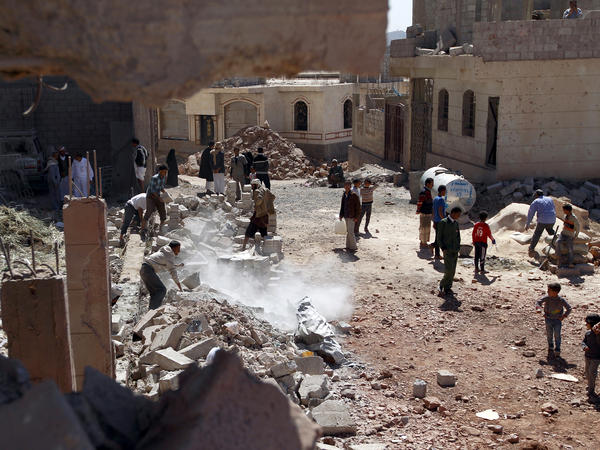 Yemeni men clear debris following an airstrike by the Saudi-led coalition in the capital, Sanaa, on Nov. 29.