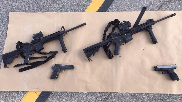 In this handout photo provided by the San Bernardino County Sheriff's Department, four guns are seen near the site of a shootout between police and suspects. The shooters left 14 people dead and 21 others wounded.