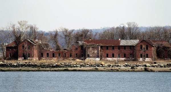 The decaying, abandoned prison workhouse on Hart Island in 2014. Each white plastic pipe near the building marks an infant mass gravesite — one plastic pipe per 1,000 babies.
