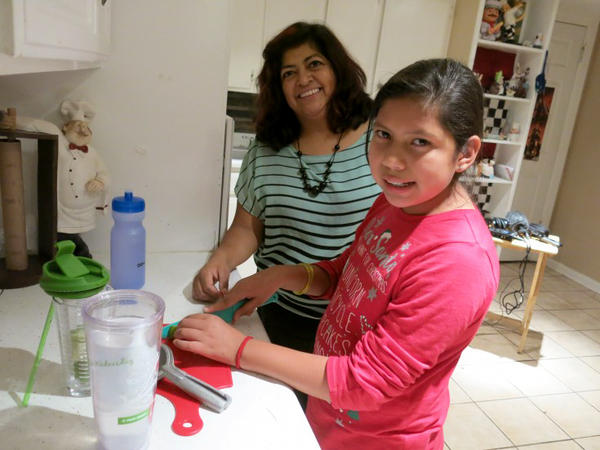 Gabriela Medina, and her daughter Andrea, in the family kitchen. The 10-year-old says she and many of her friends at school have started drinking less soda and more water they bring from home.