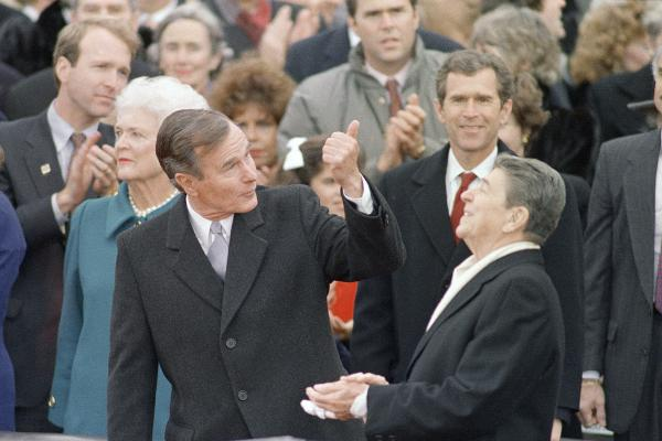 George H.W. Bush speaks with President Ronald Reagan, prior to being sworn in as the 41st president of the United States on Jan. 20, 1989. His son George W., later the nation's 43rd president, looks on, with his brother Jeb behind.