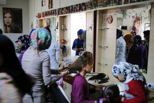 Syrian women take a free course on hairdressing at the Elbeyli Refugee Camp on Turkey's southern border with Syria. Administrators say the camp costs the Turkish government $3 million per month to run.