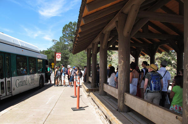 Tourists at Grand Canyon National Park in northern Arizona wait for a shuttle bus in 2015. For years, the Grand Canyon and other big national parks have been seeing rising attendance.