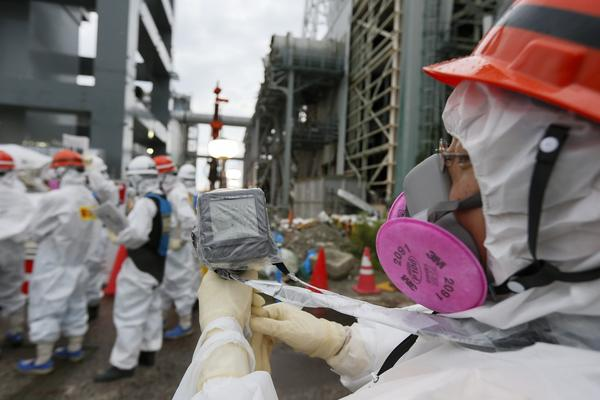 A Tokyo Electric Power Co. staffer measures the radiation level as others work on the construction of an ice wall at the Fukushima Dai-ichi plant on July 9, 2014.