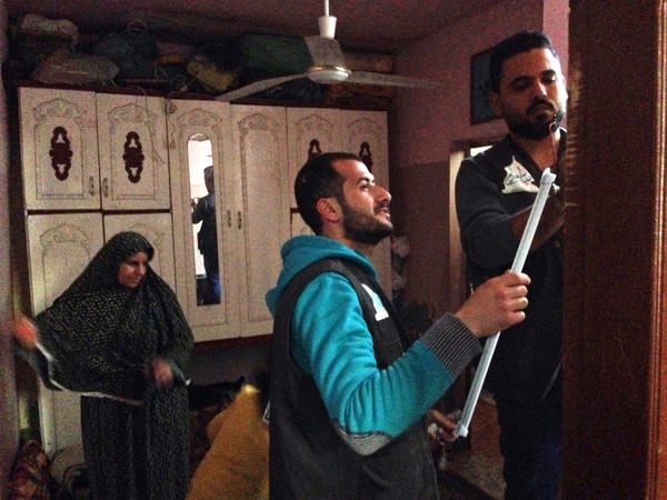 The We Are Here To Make You Happy team installs battery-operated lights, necessary during frequent power outages, at a home in Gaza.