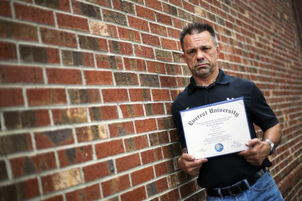 "Shane Satterfield, a roofer who owes more than $30,000 in debt for an associate's degree in computer science from one of the country's largest for-profit college companies that failed in 2014, holds his diploma in Atlanta. ""I graduated in April at the top of my class, with honors,"" says Satterfield. ""And I can't get a job paying over $8.50 an hour."""