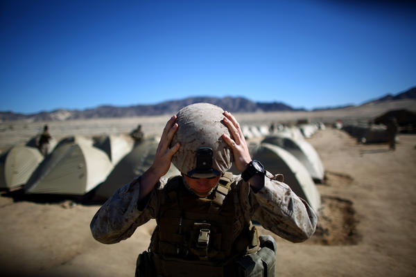 Sgt. Kelly Brown adjusts her helmet before a weapons check last year at the Marine Base at Twentynine Palms in the Mojave Desert, Calif. The Marine Corps set up a months-long training exercise to determine whether women could serve in ground combat jobs like artillery, armor and infantry. Women are now eligible to apply for these positions, but so far, none has signed up.
