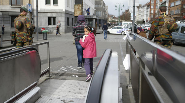 A child looks back down the exit from the subway as two soldiers stand watch. While the Brussels airport remains closed, some subways stops have reopened.