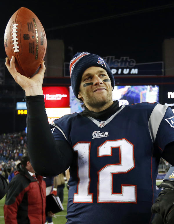 Patriots quarterback Tom Brady holds the game ball after a playoff game against the Ravens in January 2015. A week later, the team would be accused of deliberately deflating footballs in the AFC Championship game against the Indianapolis Colts.