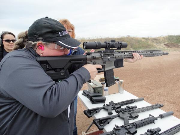 Robyn Sandoval, executive director of A Girl & A Gun, aims a rifle.