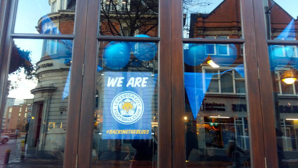 "Shop and restaurant windows in Leicester's city center are adorned with ""Backing the Blues"" posters in support of the hometown soccer team Leicester City."