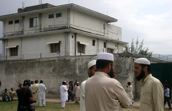 Local residents and media are seen on May 5, 2011, outside the house where Osama bin Laden was caught and killed days earlier in Abbottabad, Pakistan.