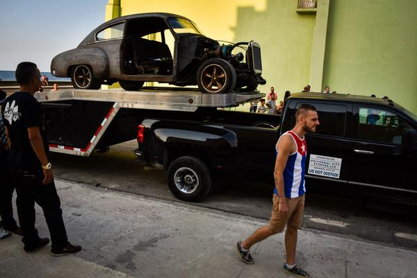 Cubans walk past cars used during the filming of <em>Fast and Furious 8</em> in Havana.