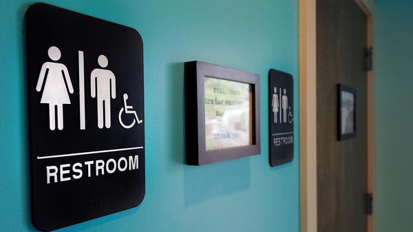 Unisex signs hang outside bathrooms at Toast Paninoteca in Durham, N.C.