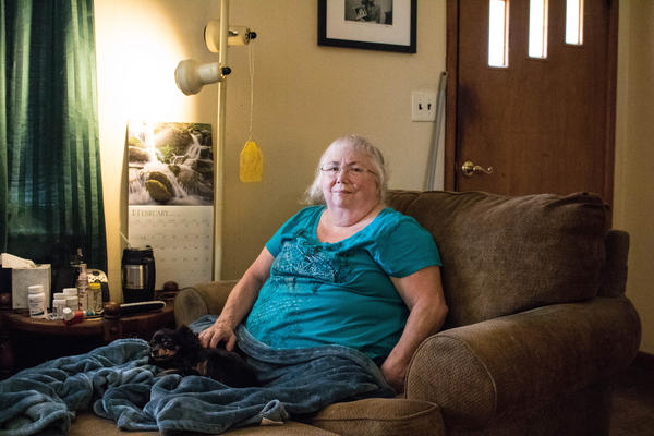 Susan Holmes sits in the living room of her home in Bokoshe, Okla. She says her asthma returned when she moved to Bokoshe, a town flanked by old coal mines.