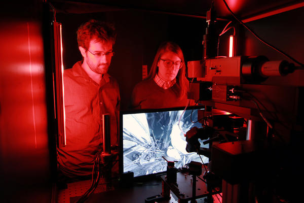 Senior scientist Jerome Lecoq and research associate Kate Roll of the Allen Institute inspect one of the microscopes used to record cellular activity in the visual cortex of mice as they watch movies.